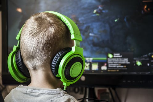 Boy playing computer game with headphones on.