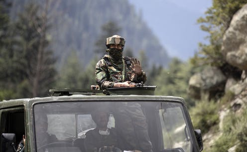 Indian soldier on top of truck with gun in Kashmir