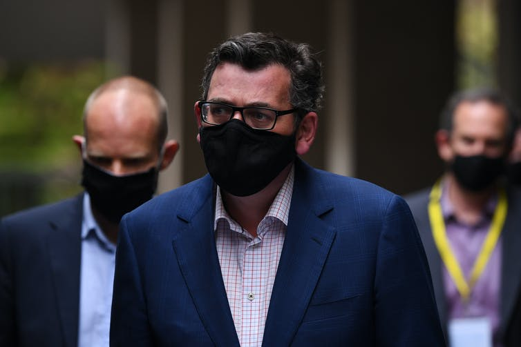 Premier Daniel Andrews walking with a mask on