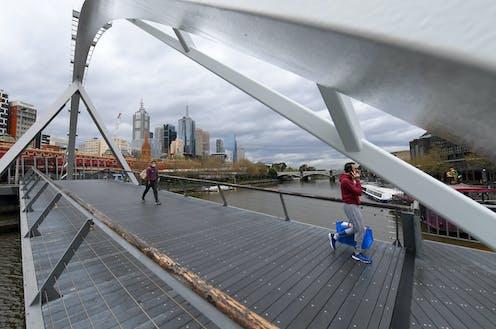 Two people walking across a footbridge in Melbourne.