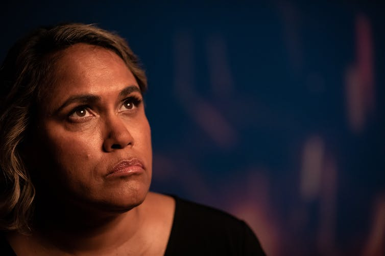 Indigenous woman looks pensive.