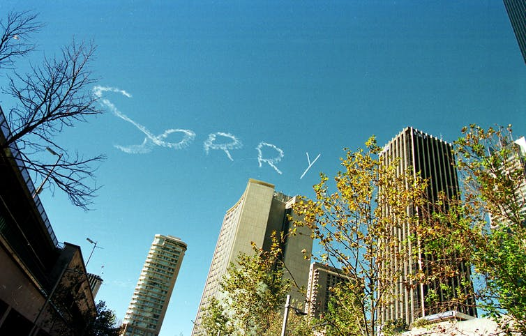 Sorry written in sky over Sydney office towers.