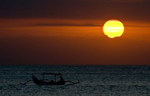 A traditional boat in the sea at a hot sunset in Bali.