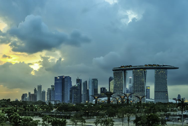 A Singapore skyline with clouds and some sun breaking through.
