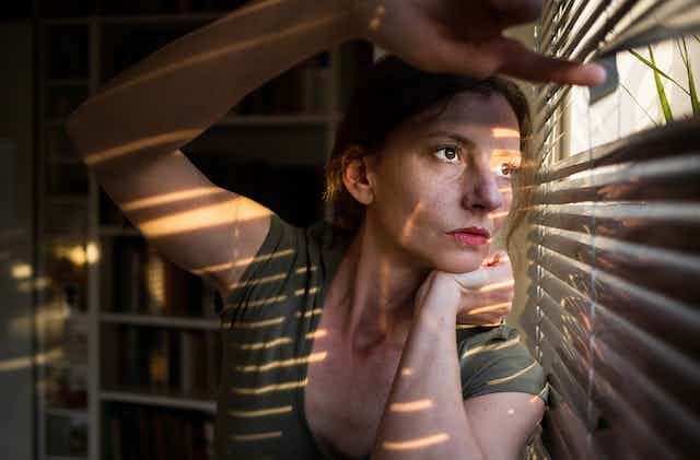 Young women in dark room looking out through venetian blinds