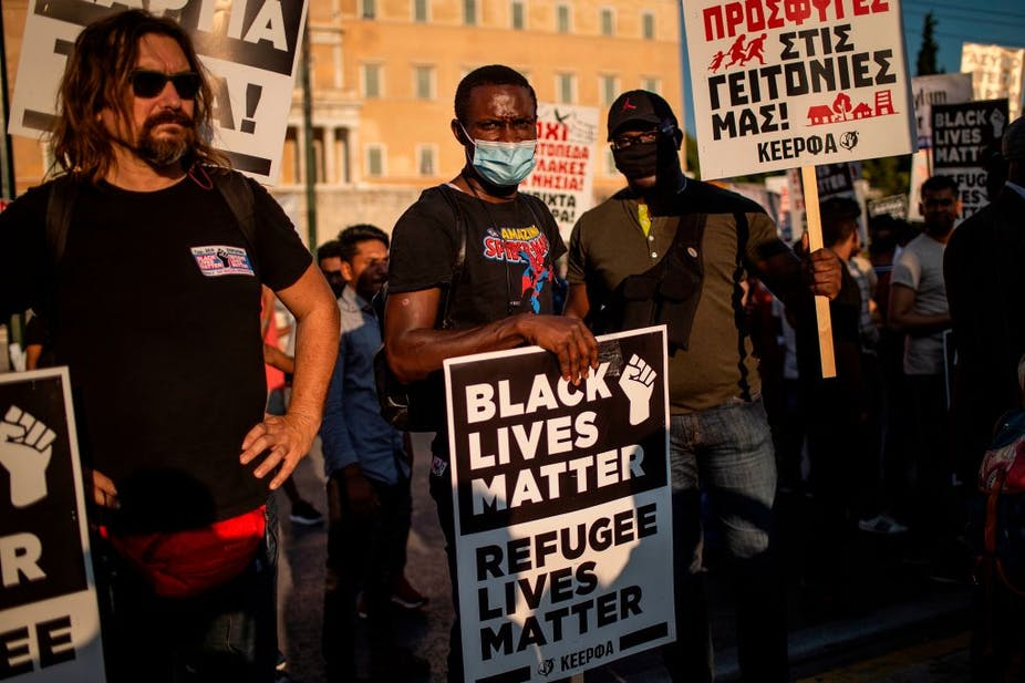 "A protester wearing a mask holds a placard reading ""Black Lives Matter, Refugee Lives Matter"" during a demonstration."