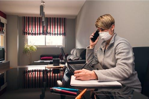 Una mujer con mascarilla habla por teléfono ante un ordenador en el salón de su casa.