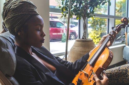 A Black woman wearing a headwrap gazes at a violin.