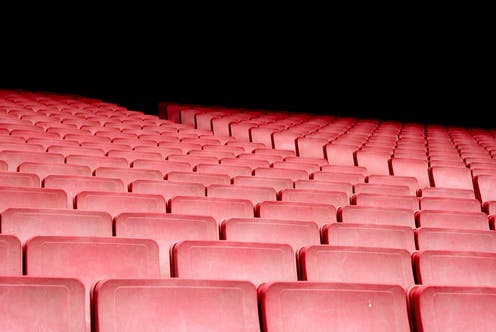 Empty red seats in an auditorium.