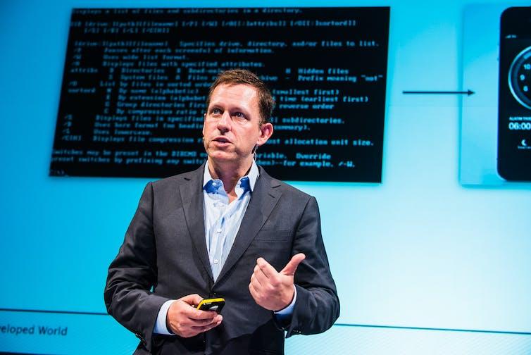 Peter Tiel stood in front of screen displaying computer code.