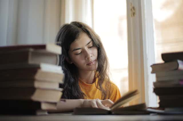 Girl reading surrounded by books