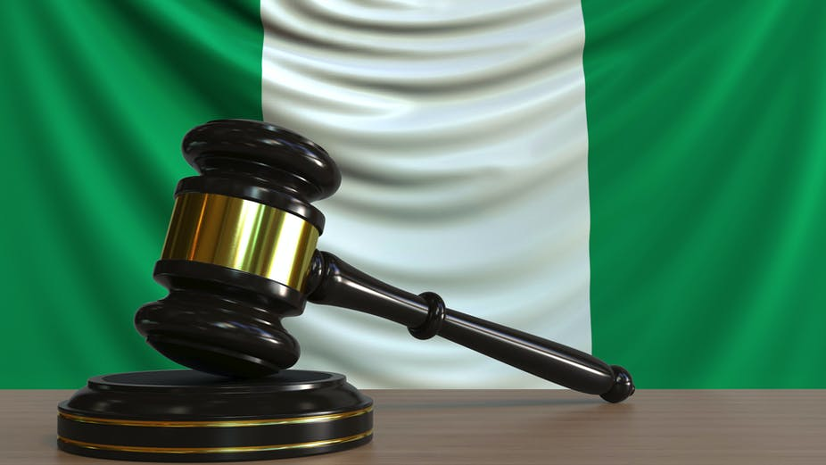 Judge's gavel and block against the flag of Nigeria