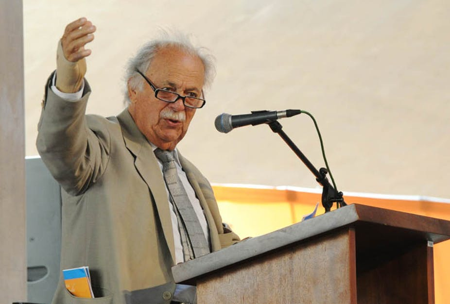 A white haired, balding and bespectacled George Bizos raises his right hand to emphasise a point during a speech