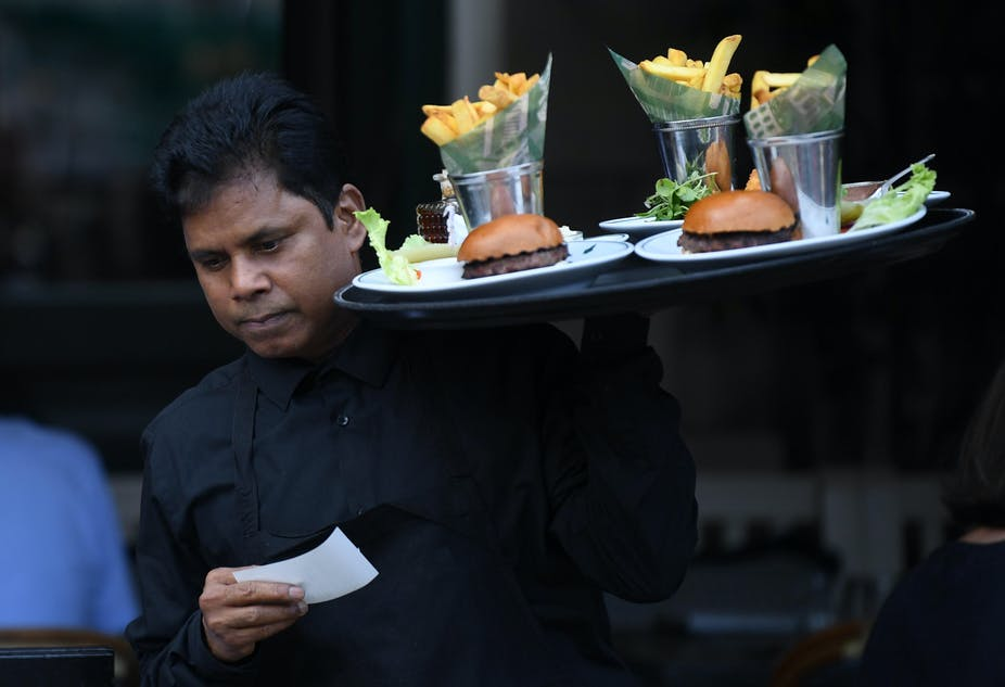 London waiter carrying tray with burgers and chips