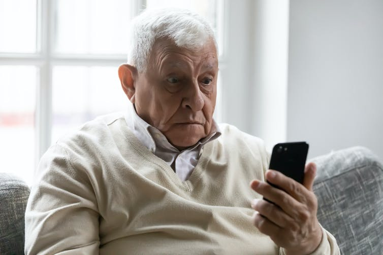 Old man sat on sofa looking confused at smartphone