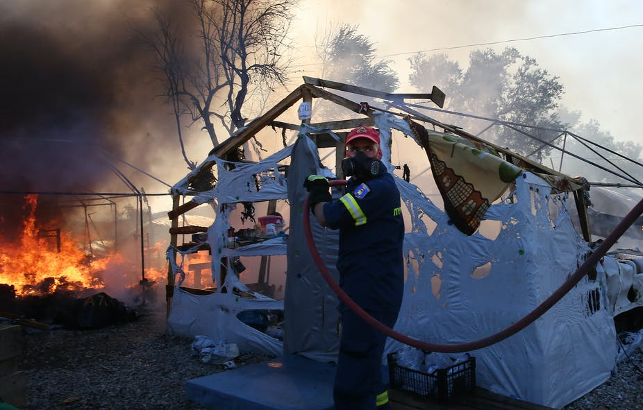 Fireman with hose in front of half burnt tent and fire.