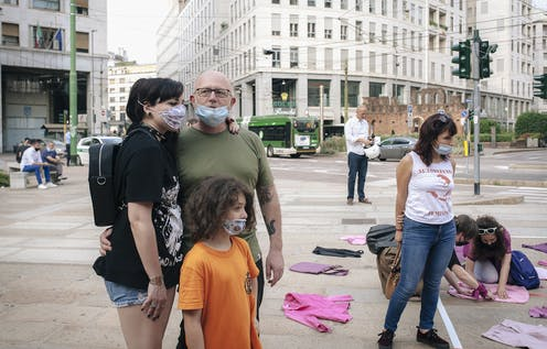 A woman, man and girl stand in a square in Milan to protest domestic violence.