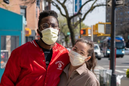 A man and woman wearing face masks pose for a picture on a sidewalk.