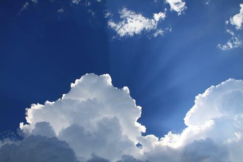 A blue sky with a fluffy cumulonimbus cloud obscuring the sun.
