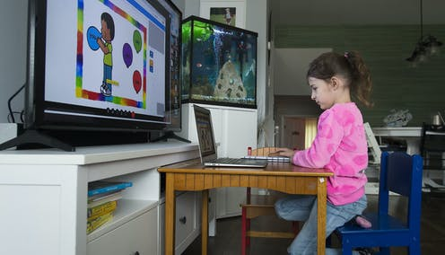 A child in front of  a laptop and large screen.