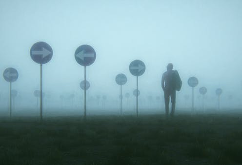 A man in a heavy mist surround by signs pointing in opposite directions.