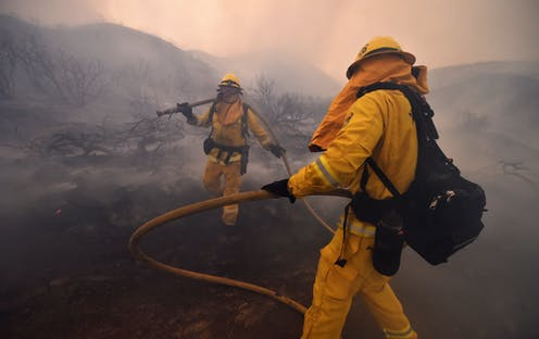 Firefighters walk through smoke during the fire at Lake Elsinore, California, in 2018.