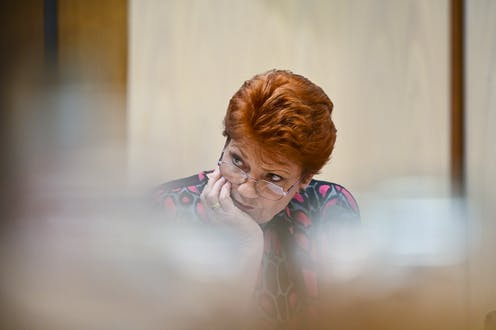 Pauline Hanson resting her head in her hand, with serious expression