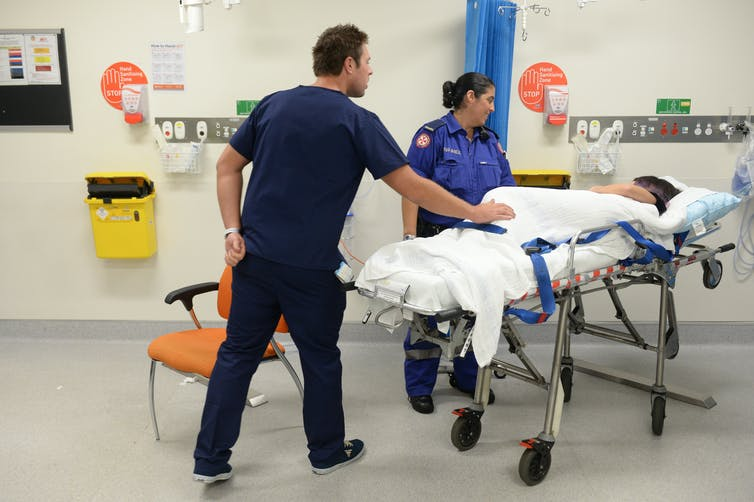 Ambulance and medical staff attend to a patient in a hospital emergency department