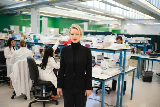 A woman dressed in black stands in a lab and looks at the camera