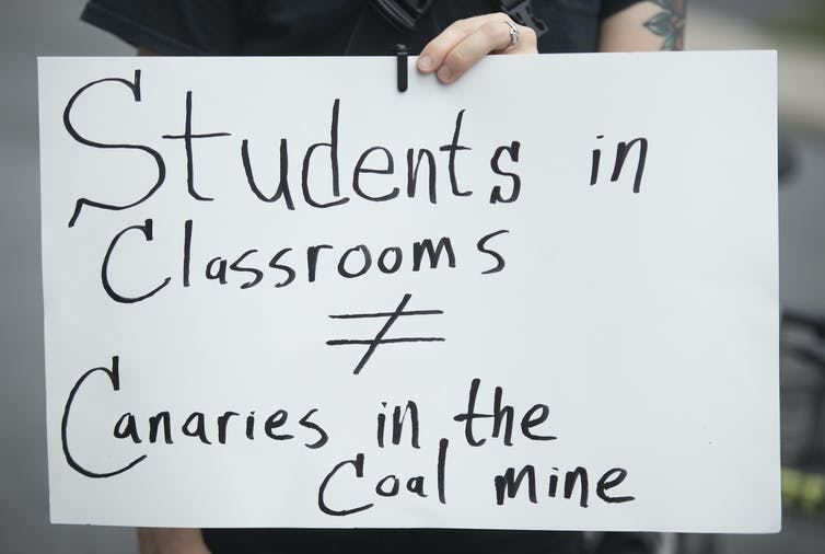 A protester holds up a sign that says Students in Classrooms do not equal Canaries in the Coal Mine