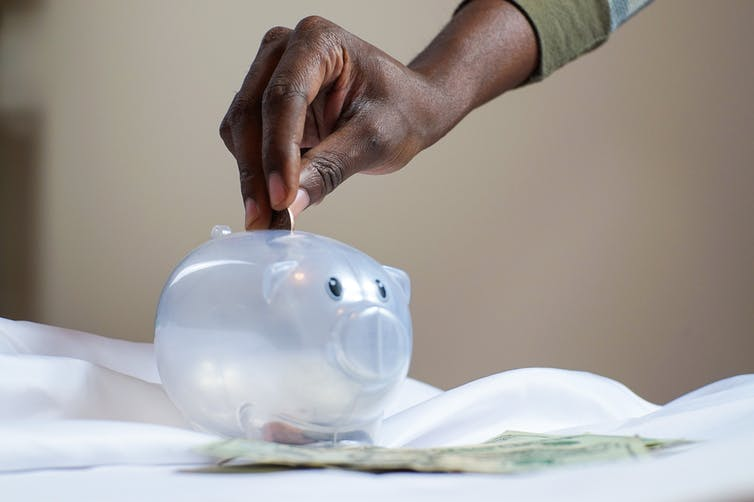 A hand drops coins into a piggy bank.