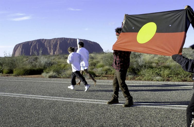 The Olympic torch is carried past Uluru
