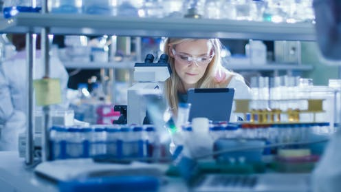A woman in a science lab looking at a tablet screen.