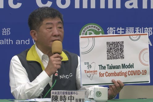 Taiwan's Health Minister Chen Shih-chung holds a sign reading 'The Taiwan Model for Combating COVID-19'.