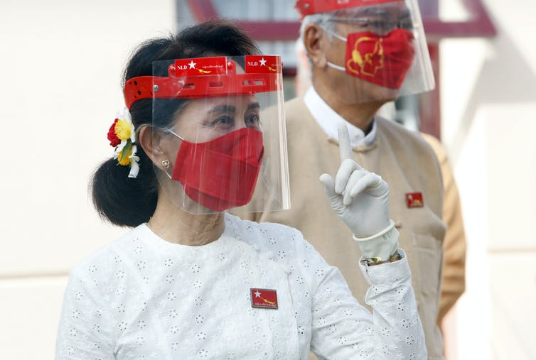 Myanmar leader Aung San Suu Kyi gestures while wearing a face shield, mask and glove.