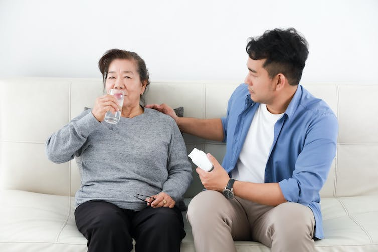 A young Asian man helping his mother with her medication. He holds a bottle of pills while his mother drinks from a glass of water as they sit side-by-side on a sofa.