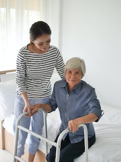 A woman helping her mother stand up with the use of a walker.