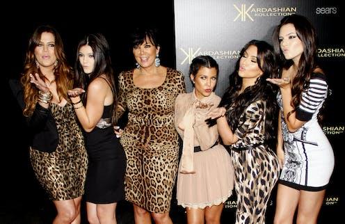 Six Kardashians wearing mostly leopard print on a red carpet.