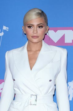 Kylie Jenner in a white belted blazer on a red carpet.