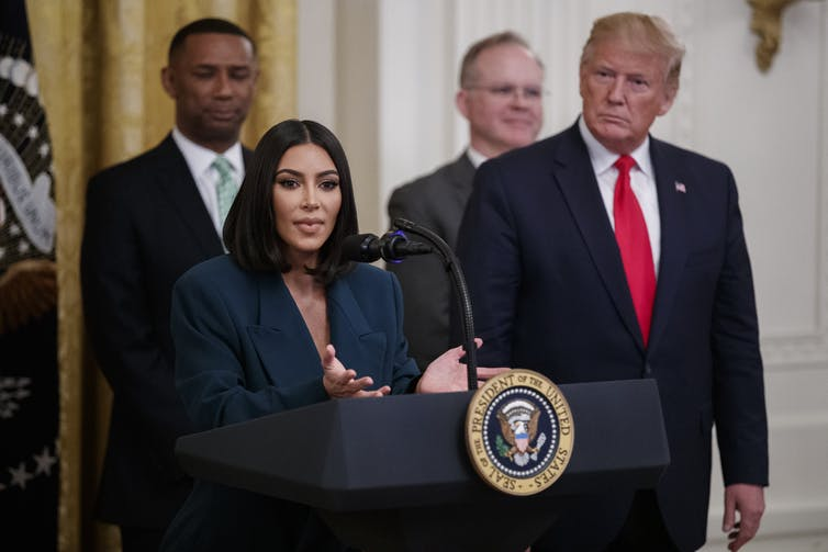 Kim Kardashian in a green suit speaking at a podium next to Donald Trump.