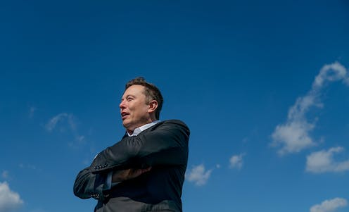 Elon Musk with arms folded, stood in front of blue sky.