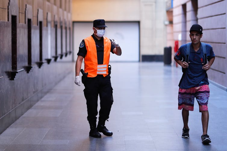 Official wearing hi-viz jacket and mask points at young man on the street.