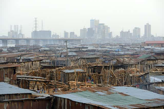 Shanty houses from wood and zinc in the foreground, sky-scraper buildings in the background, a bridge between them,