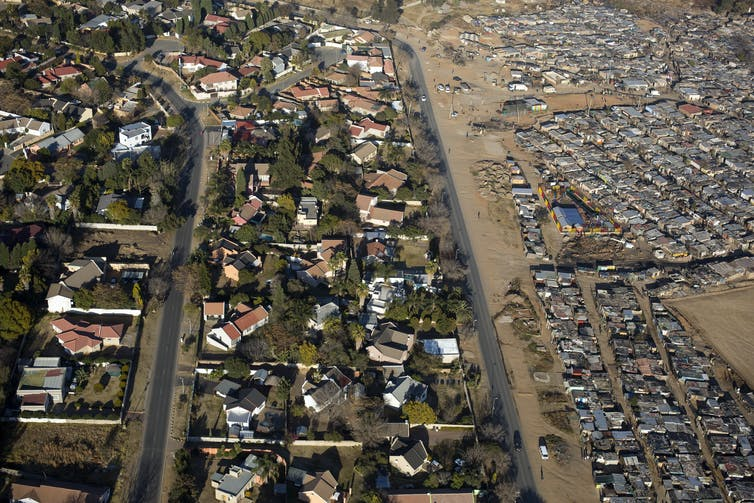 An aerial view shows a mass of shacks on one side and a green, spread out suburb on the other, divided by a wall.