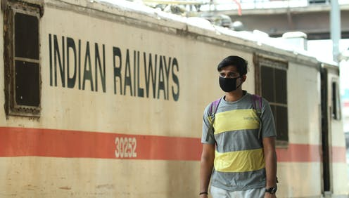Un hombre con mascarilla negra en un andén ante un vagón con el texto Indian Railways.