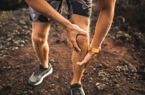 Runner holding his knee in pain