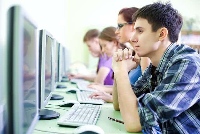 Cinco estudiantes sentados en línea delante de sendos ordenadores.