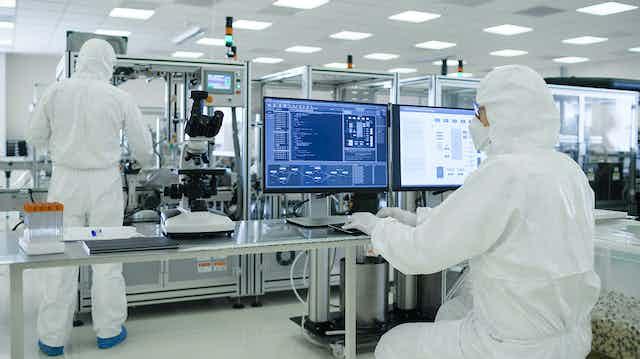 Dos científicos con monos en un laboratorio farmacológico.
