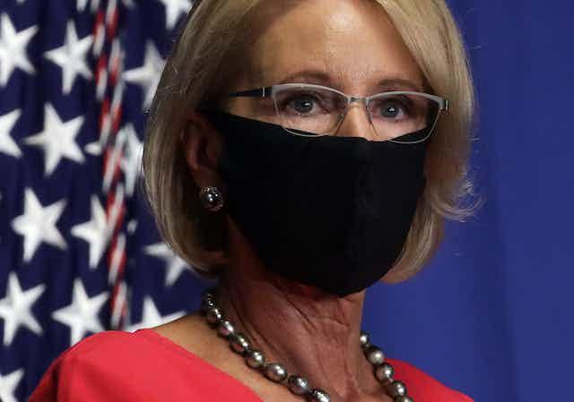 Education Sec. Betsy DeVos, wearing a face mask near an American flag