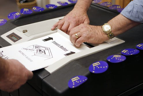 A person's hand feeds a ballot into a scanner while another person's hands help